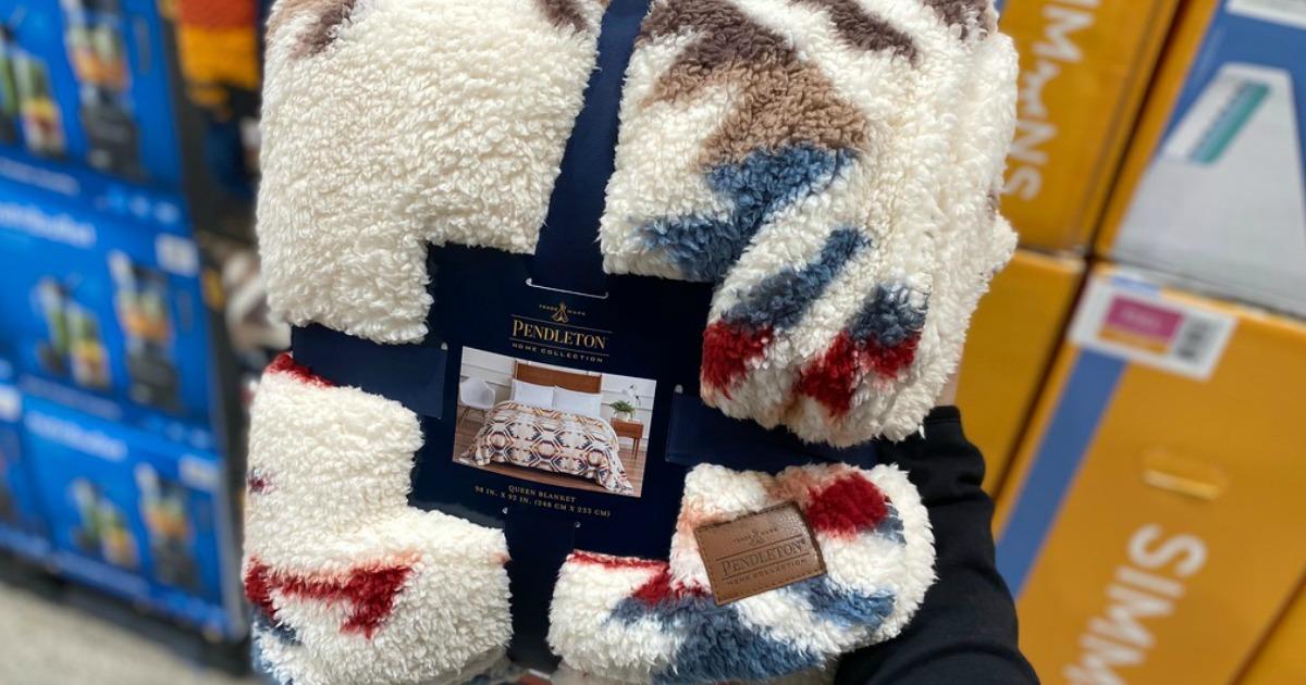 pendleton cozy sherpa blanket in packaging beind held in store
