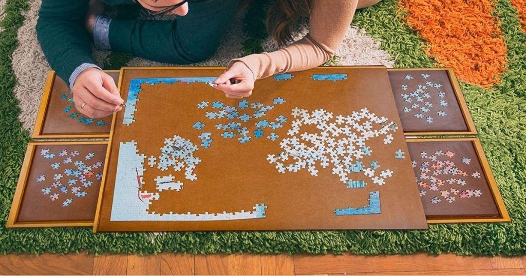 pria dan wanita menyusun puzzle di papan puzzle
