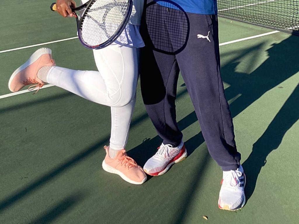 wanita yang memegang raket tenis dengan sepatu tenis berwarna merah muda