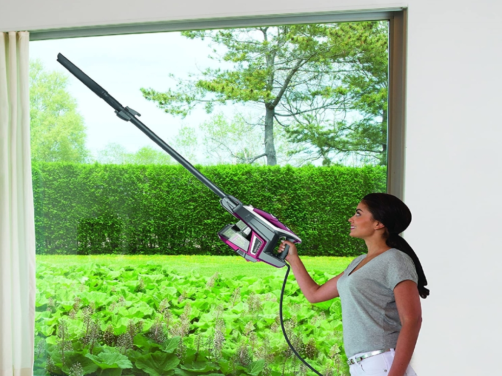 woman vacuuming her curtains