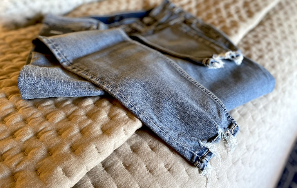 silver jeans sitting on quilt