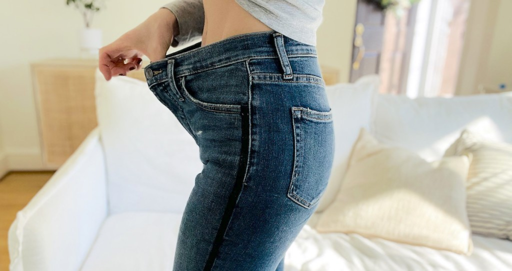hand pulling waist from jeans