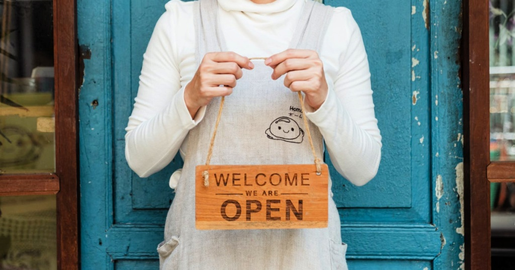 small business woman holding welcome sign