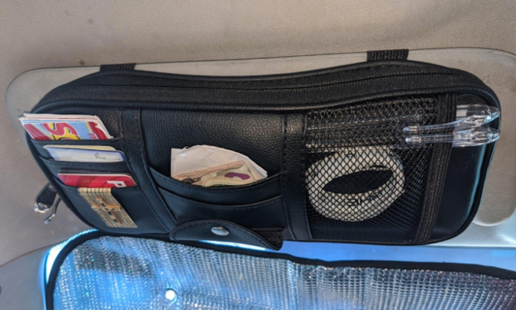black mesh car organizer with credit cards wires and other accessories