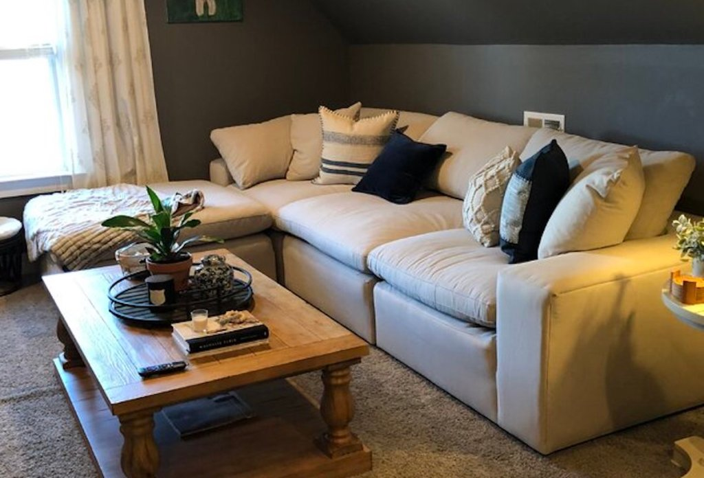 tan sectional couch sitting in styled living room with wood coffee table