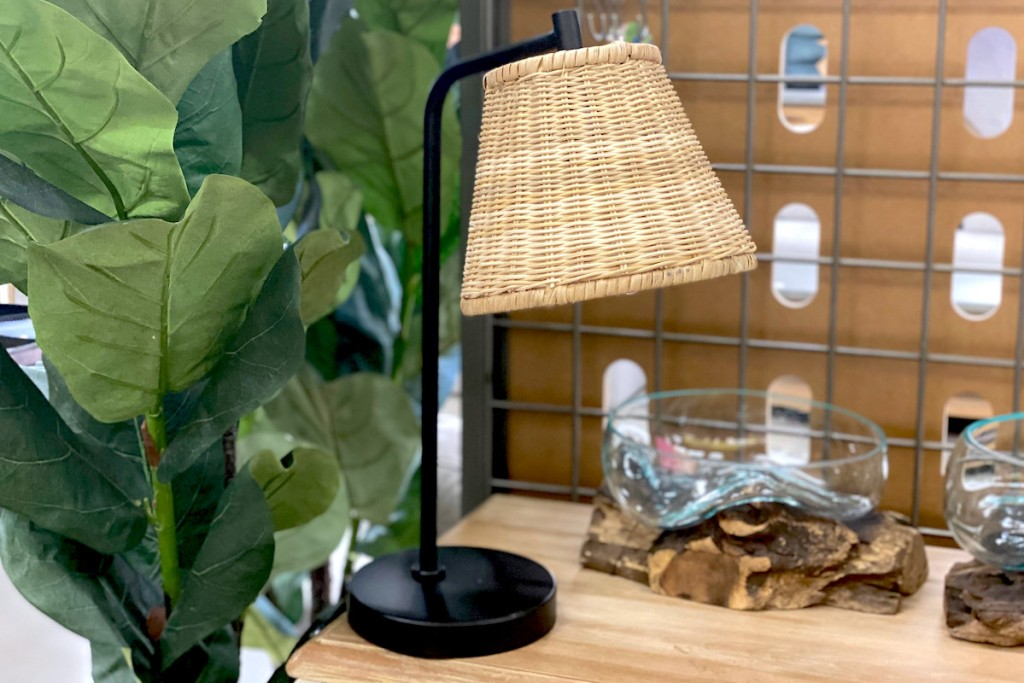 black and wicker table lamp next to faux fig tree