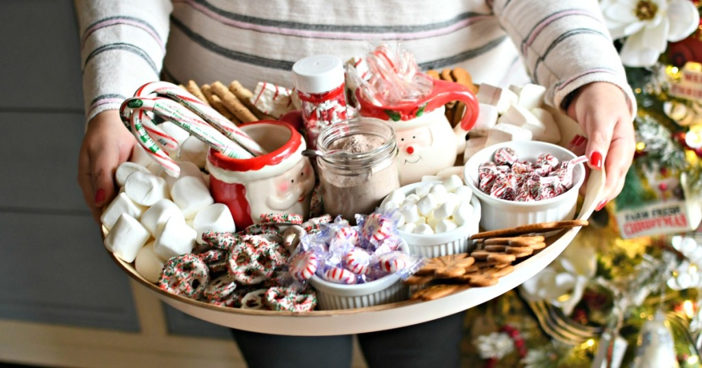 woman holding a hot cocoa charcuterie board