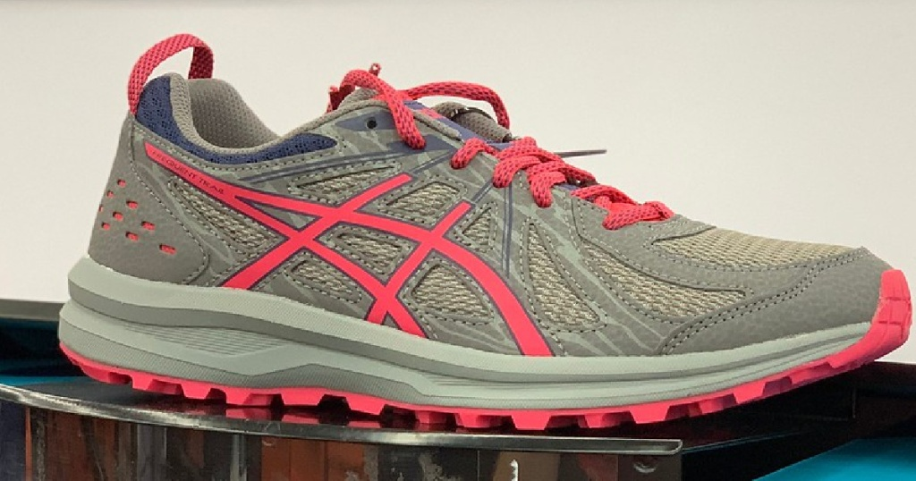 pair of women's running shoes in pink and grey in store