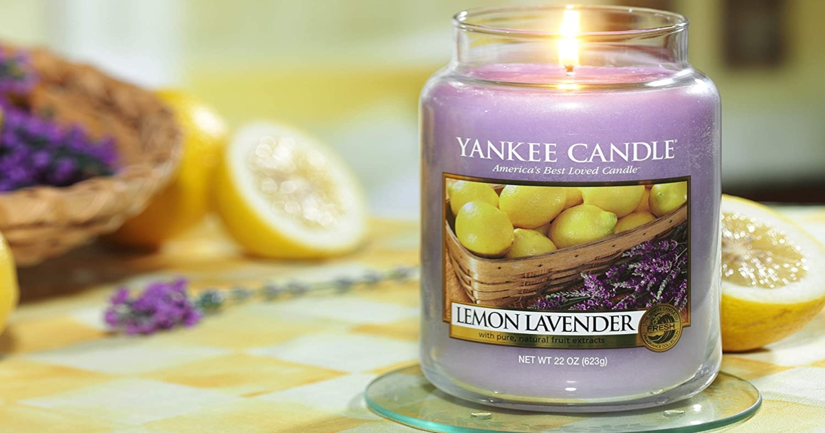 lemon lavender yankee candle on a table. It is lit and sitting on a table with a yellow table cloth