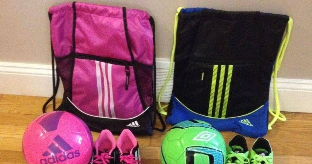 two Adidas bags with soccer balls and cleats