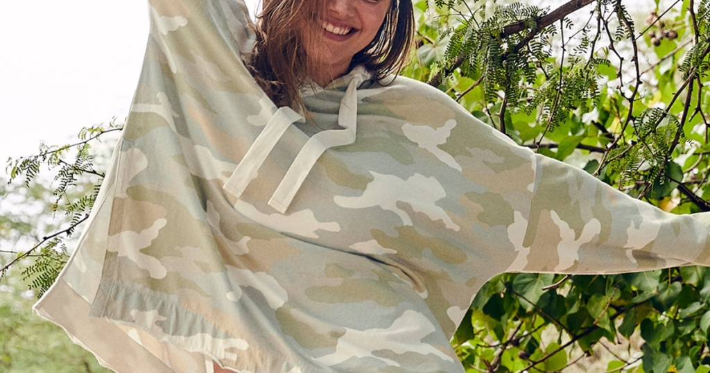 woman in green camo hoodie with trees in background