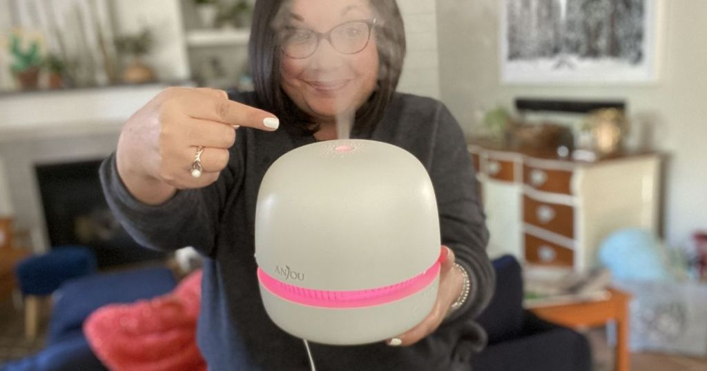 woman holding an essential oil diffuser