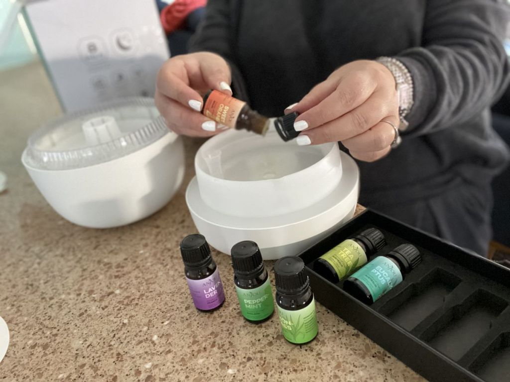woman pouring essential oil into a diffuser