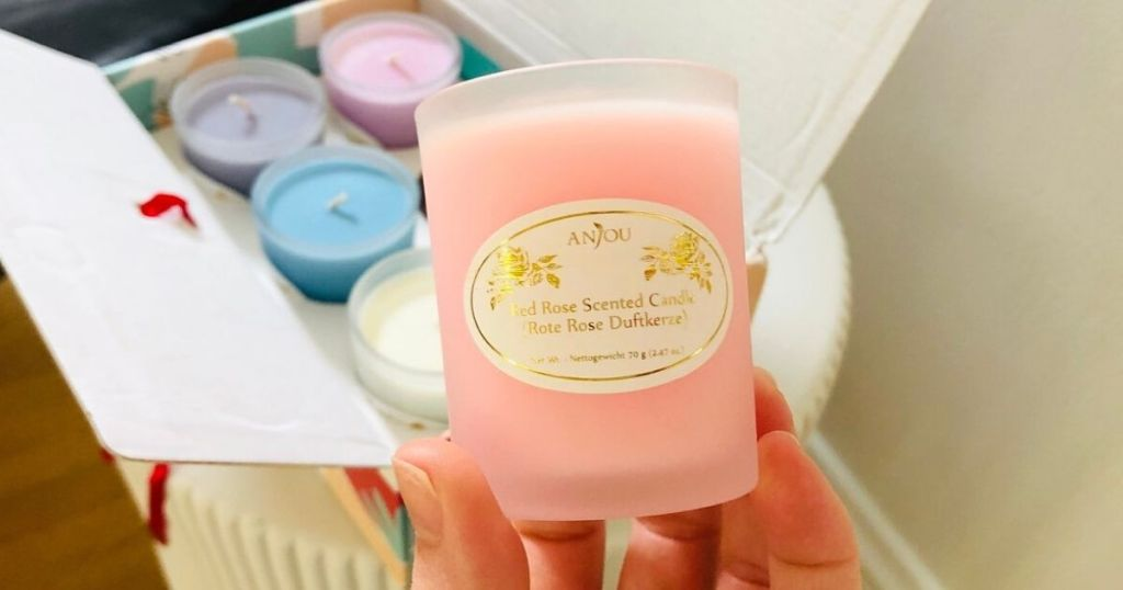 hand holding pink Anjou rose candles
