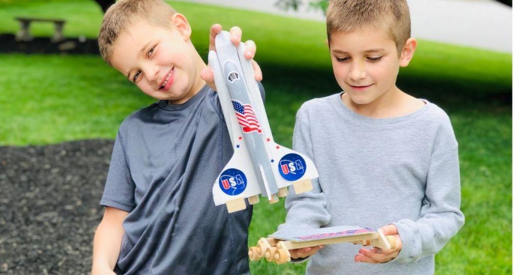 two kids holding a rocket ship