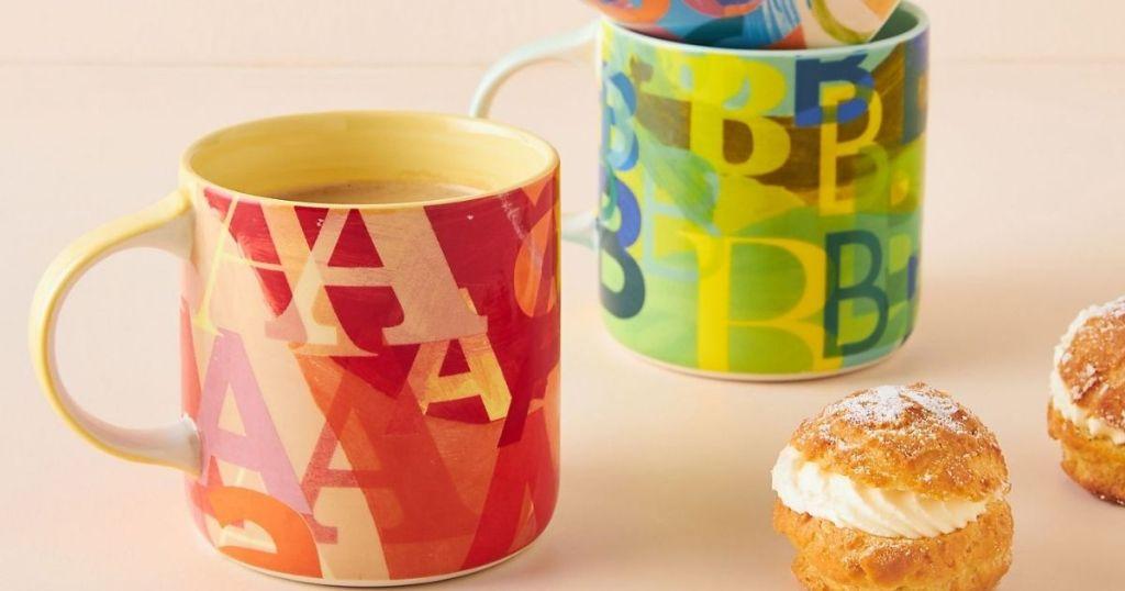 mugs with cream puffs next to them