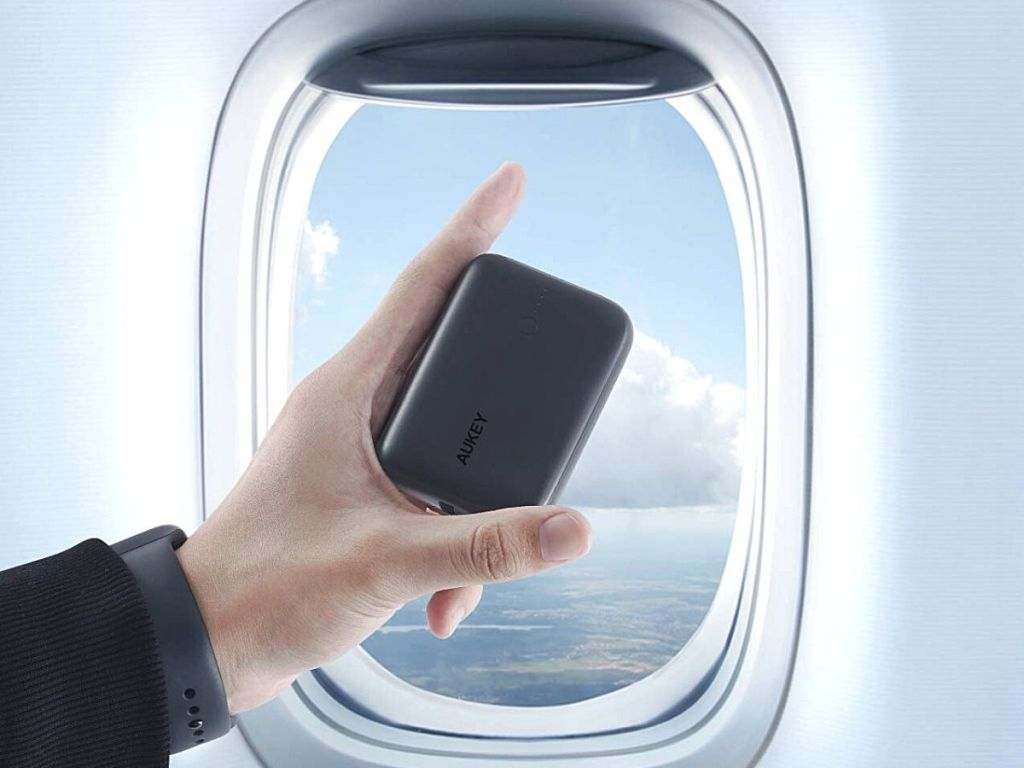 hand holding portable charger in front of airplane window