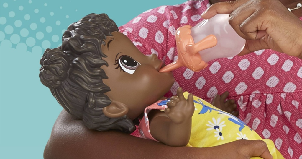 girl feeding baby doll with toy bottle