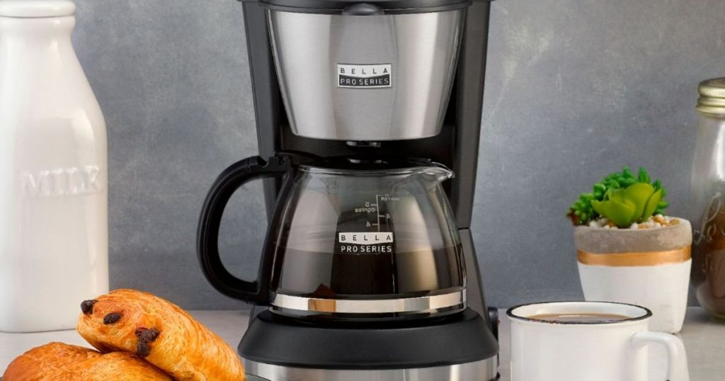coffee maker with cup and scones by it