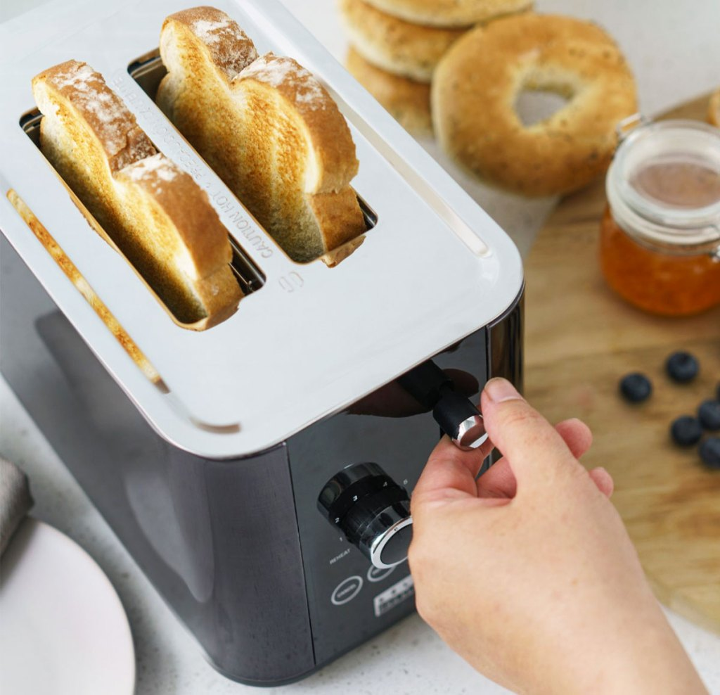 person adjusting knob on toaster with two slices of toasted bread inside