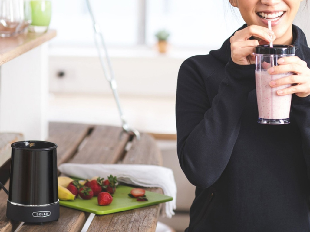 woman holding a blender smoothie cup