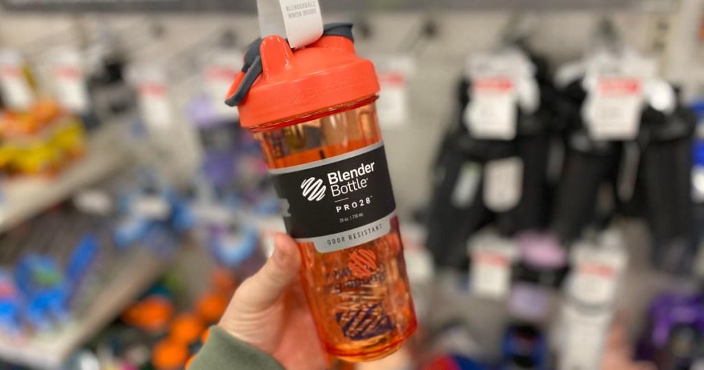 hand holding orange blender bottle
