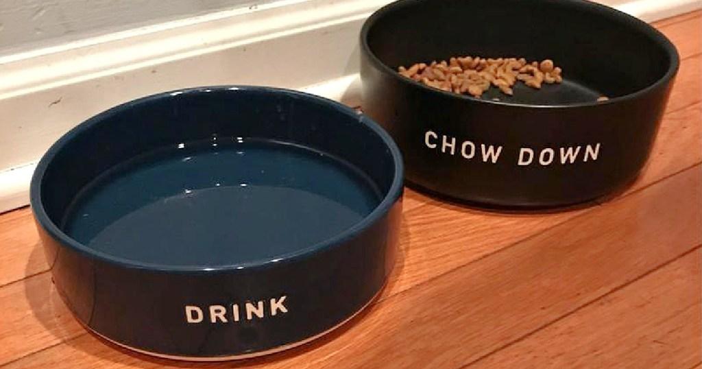 blue dog drink bowl and black food bowl on wood floor