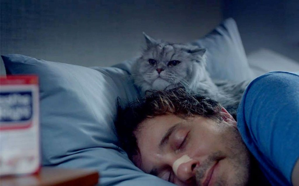 man in bed sleeping with breathe right nasal strip on his nose and cat laying at his head