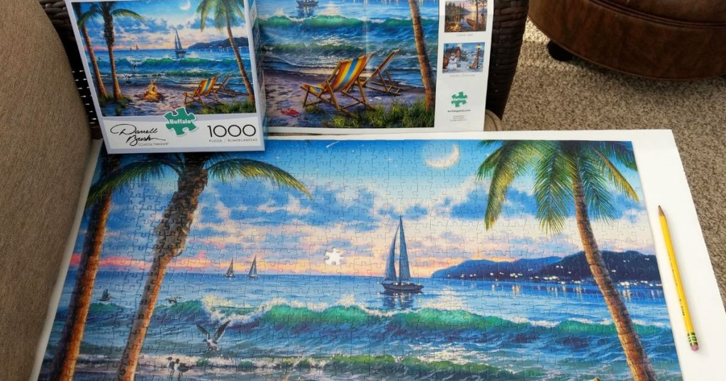 puzzle of beach scene completed on table with the box in background
