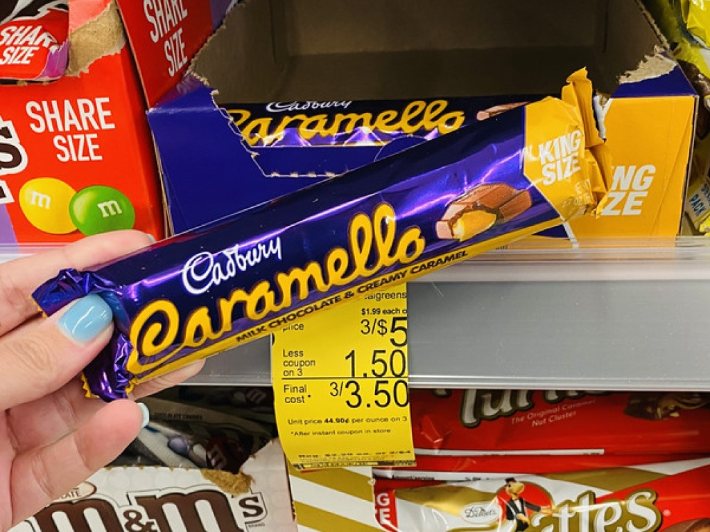 woman's hand holding caramel candy bar in store