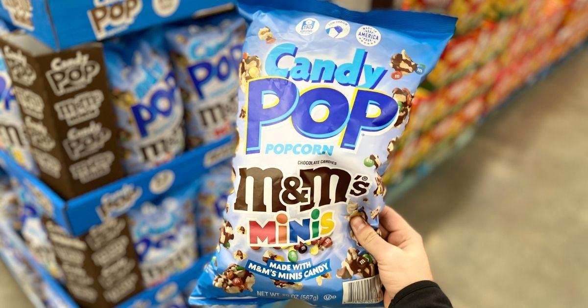 hand holding Candy Pop M&M's Minis Popcorn