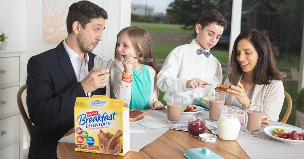 family sitting at table with a box of carnation breakfast essential