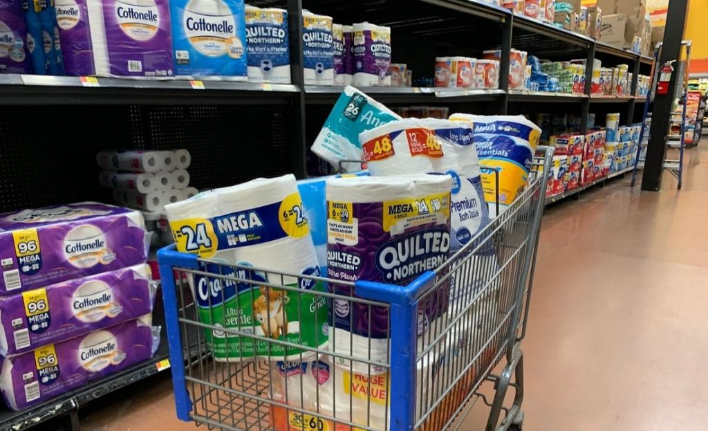 A grocery cart full of bath tissue at a store