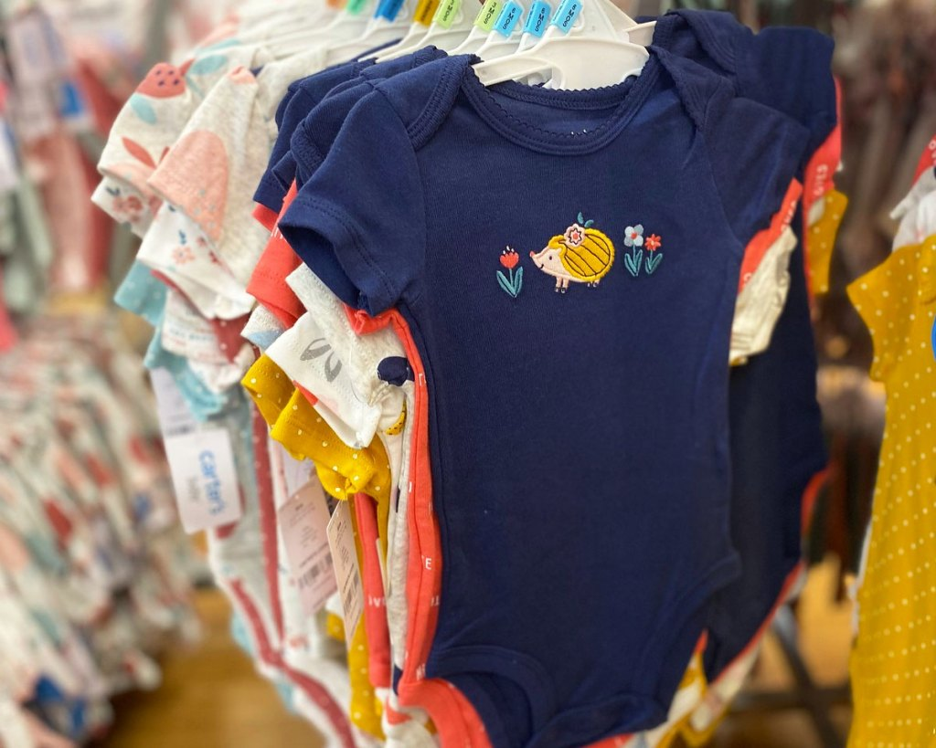 carter's baby girls bodysuits on hangers on store display