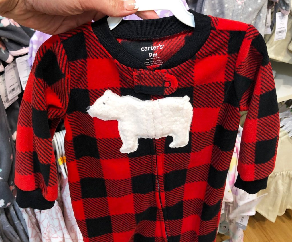 person holding up a red and black buffalo check carter's baby onesie with a white polar bear