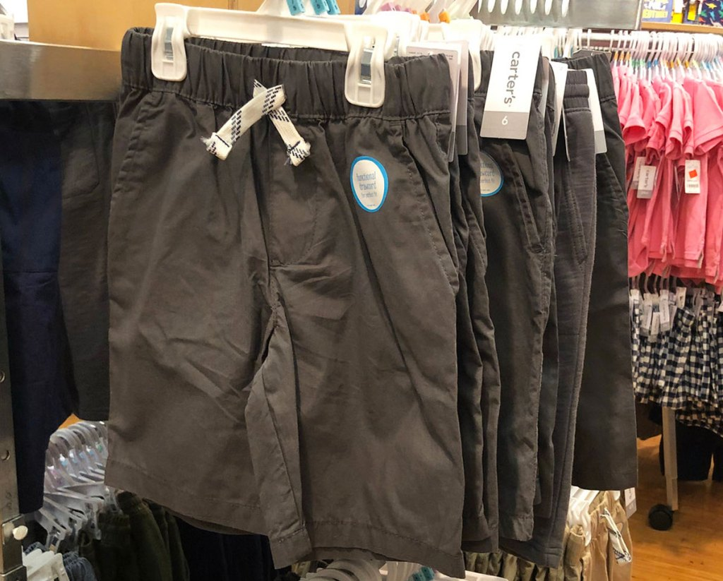 grey pairs of carter's boys shorts hanging on hangers on store display
