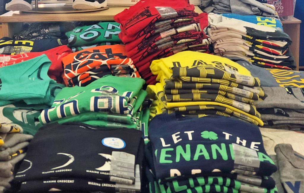 stacks of folded boys graphic tees on display table