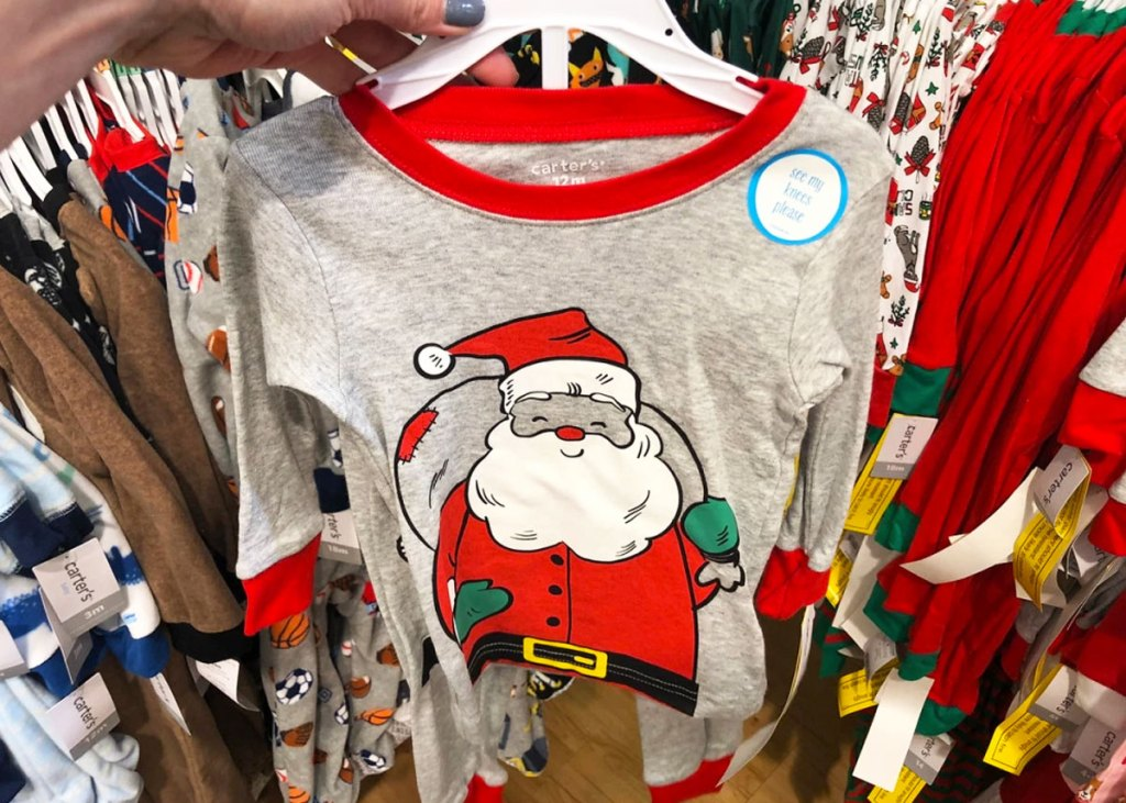 person holding up a grey and red set of carter's kids pajamas with santa on them