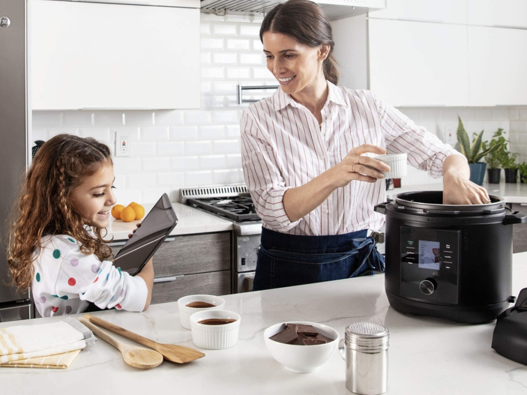 little girl and woman standing in a kitchen next to a pressure cooker