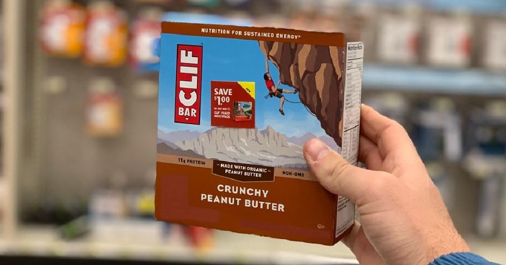 man's hand holding box of crunchy peanut butter energy bars