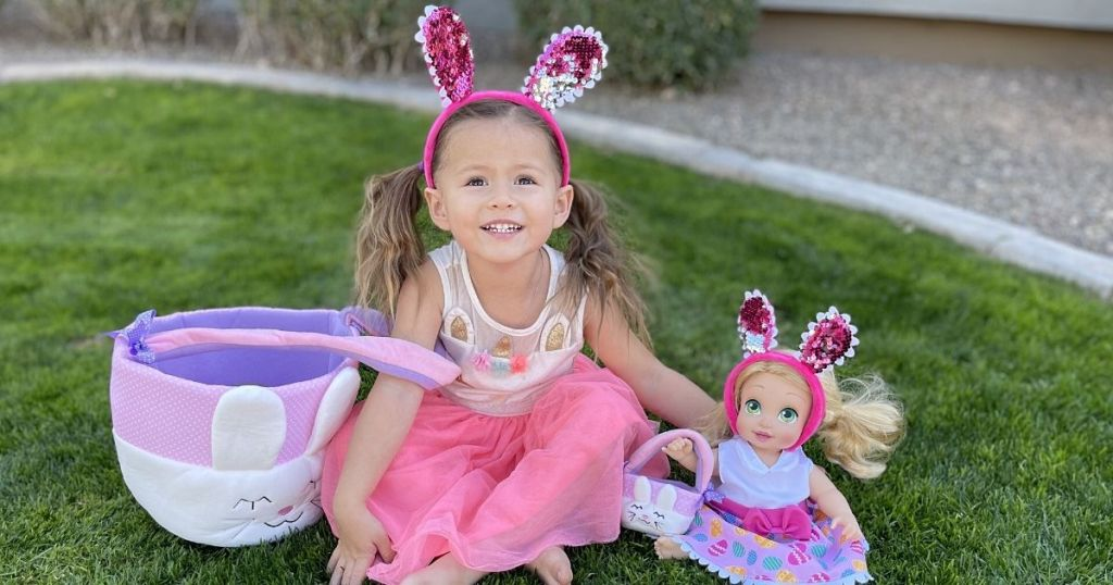 little girl and doll waring matching bunny ears and carrying matching bunny baskets