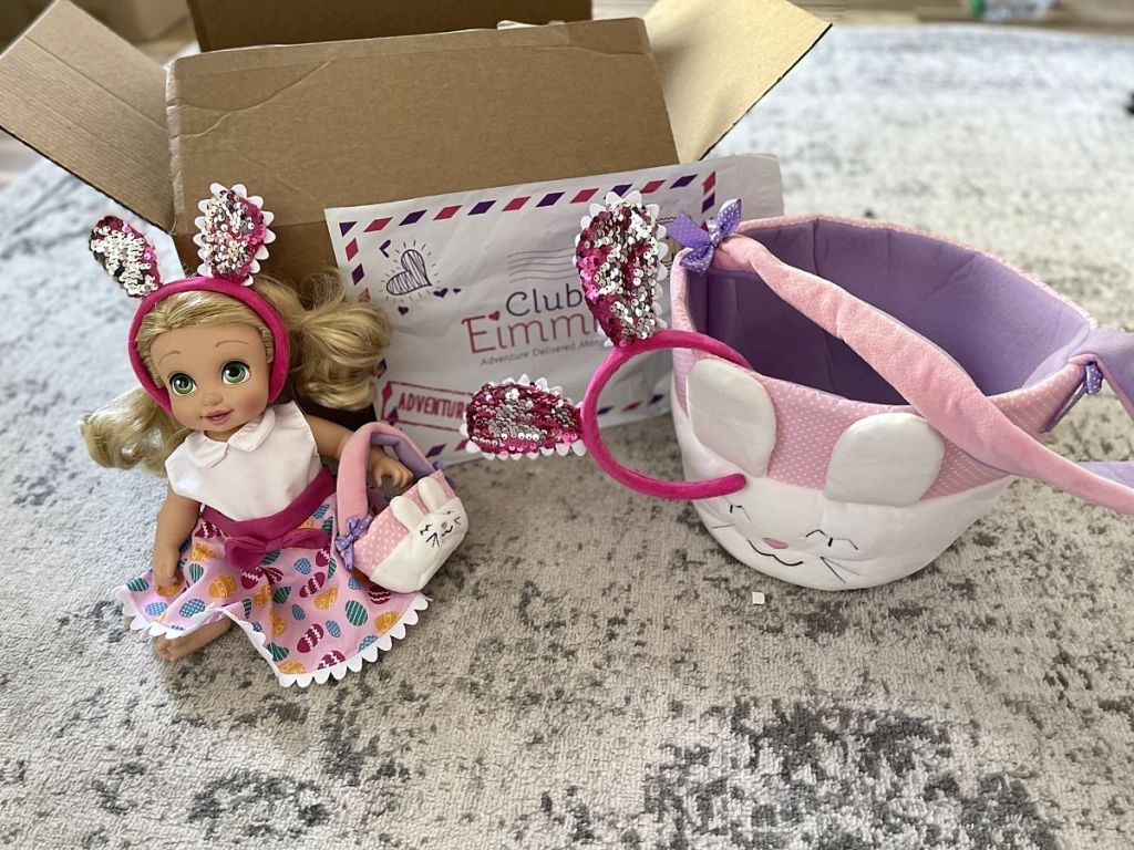 doll wearing bunny headband, dress and carrying a basket next to larger bunny basket and bunny ears