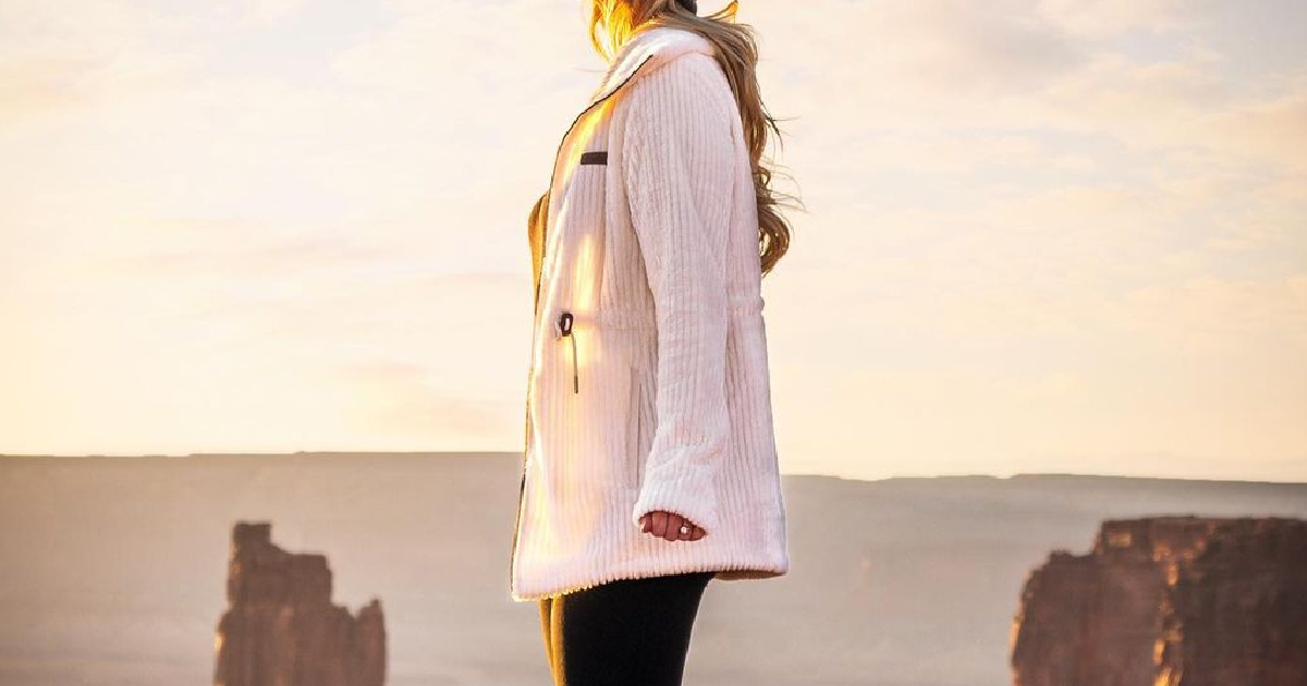 woman in white sherpa jacket with valleys in background