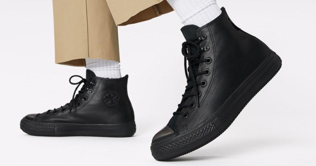 man wearing black converse boots