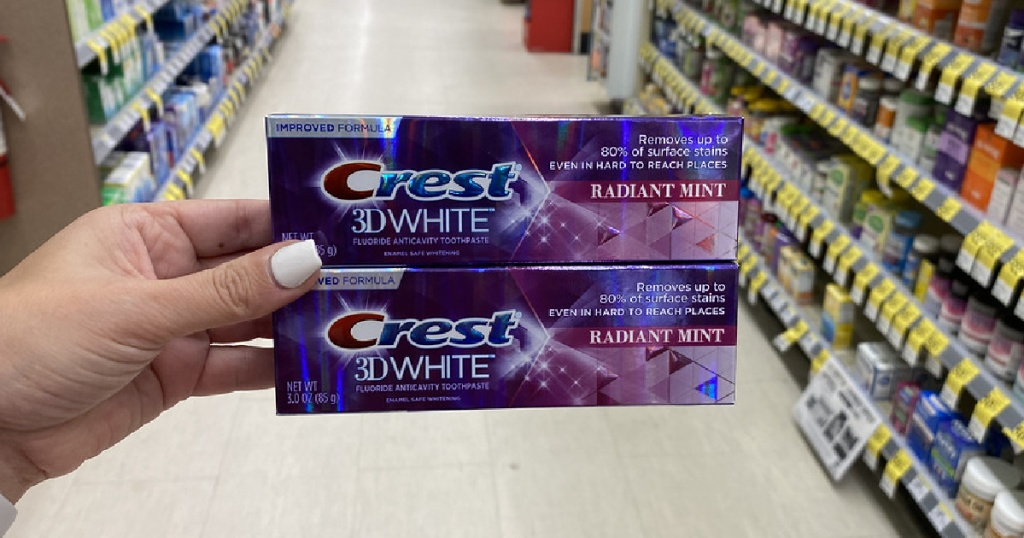 woman's hand holding two boxes of toothpaste in store