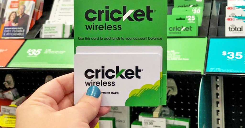 person holding up white and green cricket wireless phone card