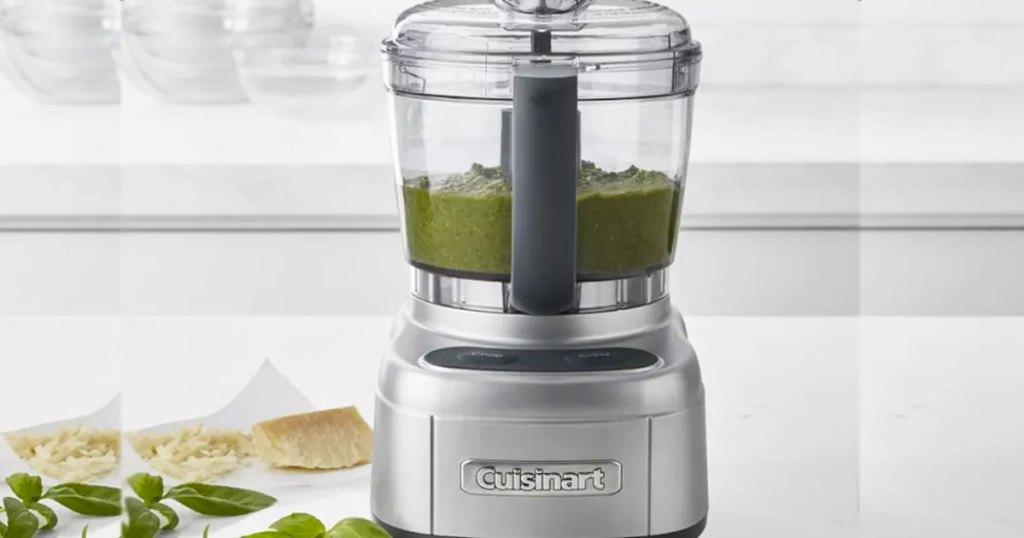 silver mini food processor on kitchen counter making pesto