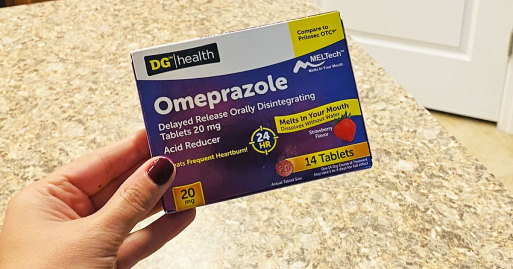 person holding up purple and white box of dollar general heartburn medication