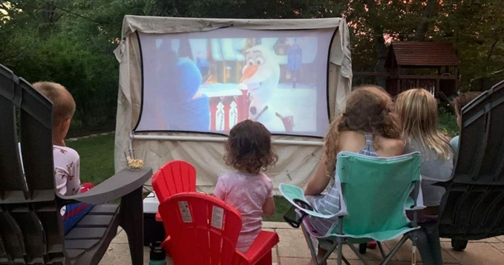 kids sitting outside watching disney frozen projected on a white screen