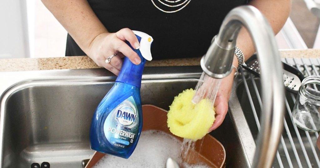 woman holding blue bottle of dawn powerwash soap spray and yellow scrub daddy sponge in kitchen sink